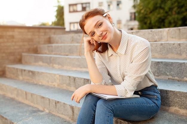 Una bella ragazza dai capelli rossi scrive una lettera d'amore romantica seduto su una scala