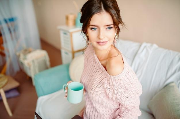 Una bella ragazza di aspetto europeo siede in un ambiente domestico accogliente con una tazza di livido in mano