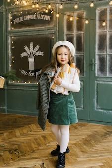 Una bella ragazza di sei anni alla moda tiene in mano un sacchetto di baguette e si trova vicino alla finestra di una panetteria con dolci freschi