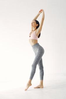 Una bella ragazza è impegnata in uno studio di yoga