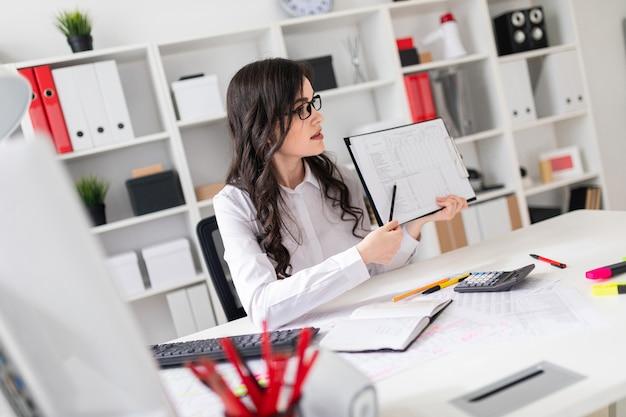 Una bella ragazza è seduto a un tavolo in ufficio e punta una matita alle informazioni nel documento.
