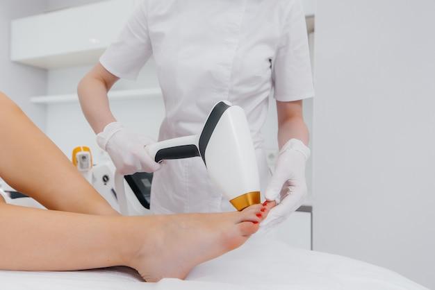 Una bella ragazza eseguirà una procedura di epilazione laser con attrezzature moderne nel primo piano del salone spa. salone di bellezza. cura del corpo.