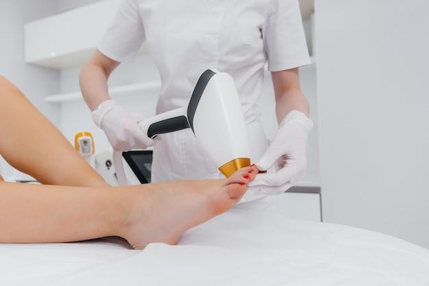 Una bella ragazza eseguirà una procedura di epilazione laser con attrezzature moderne nel salone spa. salone di bellezza. cura del corpo.
