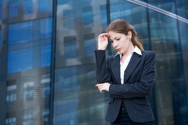 Una bella ragazza in abito e camicia bianca sta pensierosa sulla strada sullo sfondo di un edificio per uffici di vetro
