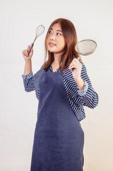 Una bella ragazza in grembiule è in piedi su un muro bianco con in mano una pala, una frusta e un mestolo