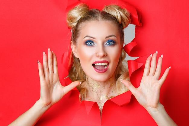Una bella ragazza in salita da un buco in carta rossa