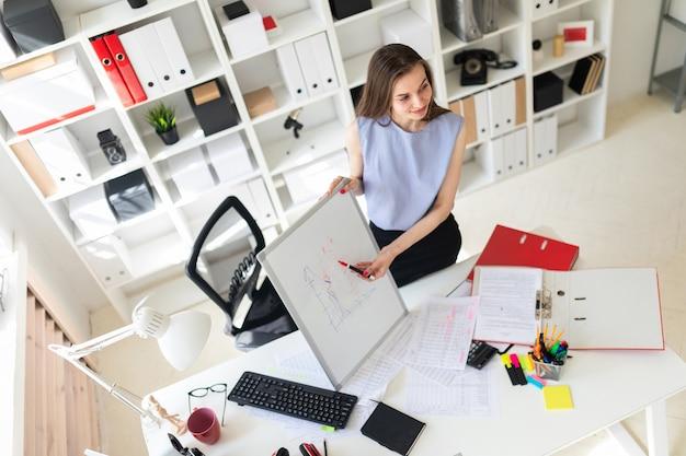 Una bella ragazza in un ufficio si trova vicino a un tavolo e spiega su una lavagna magnetica una ghiaia.