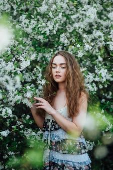 Una bella ragazza in un vestito si trova accanto a un bus di ciliegio in fiore