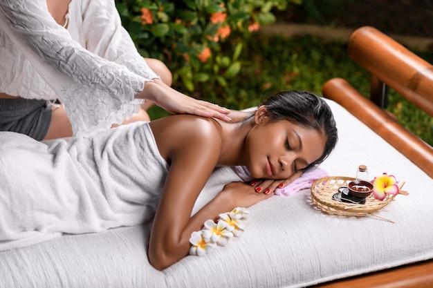 Una bella ragazza interrazziale giace con gli occhi chiusi su un lettino da massaggio con un cestino con oli aromatici e un piccolo fiore e riceve un massaggio alla schiena