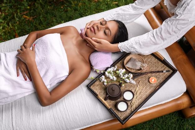 Una bella ragazza interrazziale giace su un lettino da massaggio su cui si trova un vassoio con aroma complesso e riceve un massaggio facciale