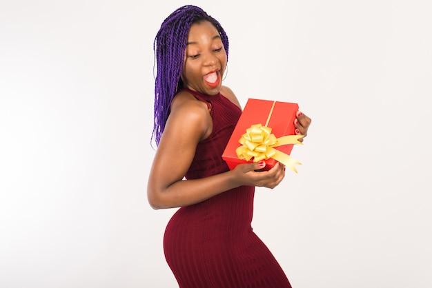 Una bella ragazza nera con abito festivo è felice di ricevere un regalo per le vacanze