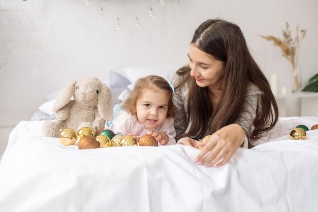 Una bella ragazza riccia di 2 anni con la sua giovane madre giace sul letto tra ghirlande e decorazioni e ride