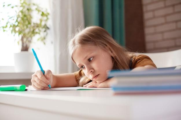 Una bella ragazza scrive con una penna su un quaderno. il bambino esegue i compiti. allenamento a casa, allenamento online