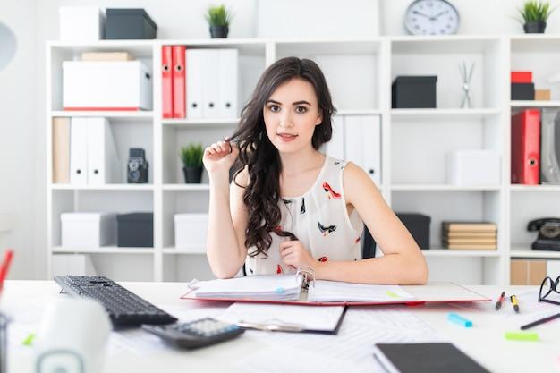 Una bella ragazza si siede al tavolo dell'ufficio, tiene i capelli in mano e sembra dritta.