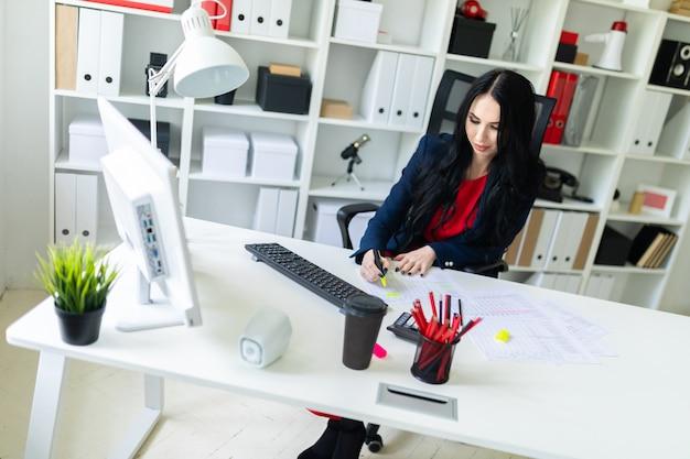Una bella ragazza si siede su una sedia a un tavolo bianco in ufficio e mette in evidenza punti importanti nei documenti con un pennarello giallo.