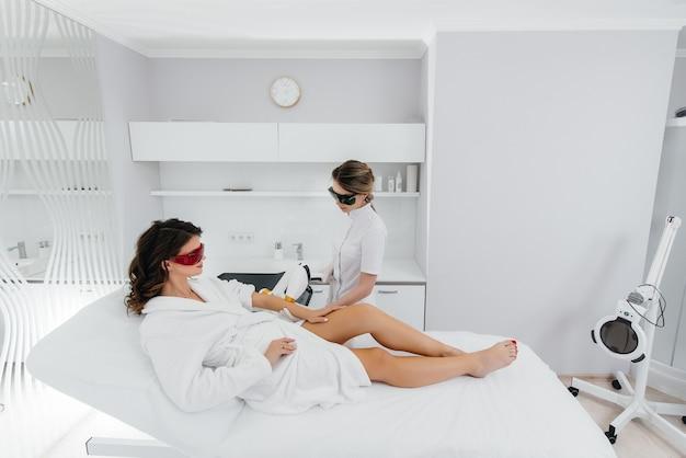 Una bella ragazza si sottoporrà alla depilazione laser con attrezzature moderne in un salone spa. salone di bellezza. cura del corpo.
