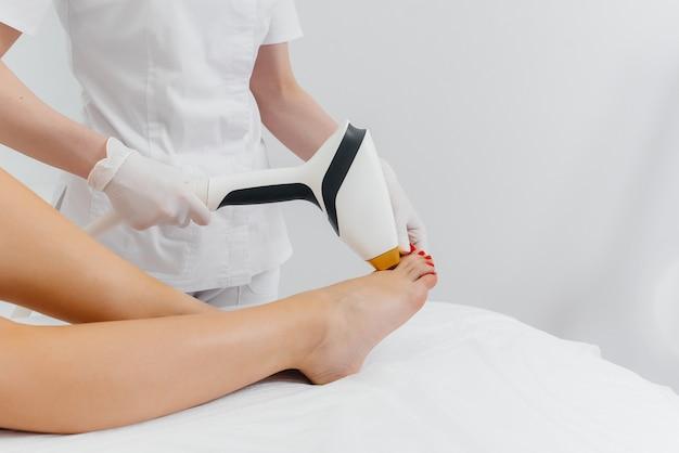 Una bella ragazza si sottoporrà alla depilazione laser con attrezzature moderne in un salone spa