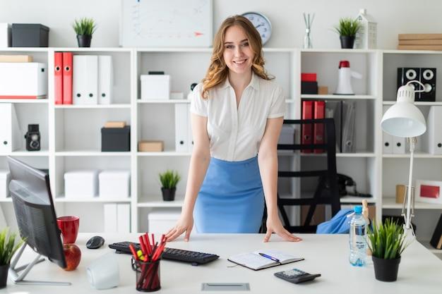 Una bella ragazza si trova in ufficio, le mani sul tavolo.