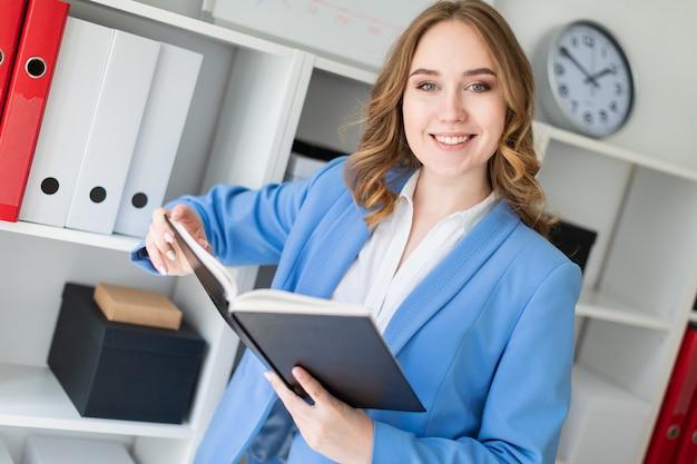 Una bella ragazza si trova vicino a un rack in ufficio e tiene un libro aperto nelle sue mani.