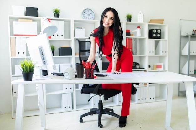 Una bella ragazza si trova vicino a una scrivania, appoggiando il piede su una sedia.