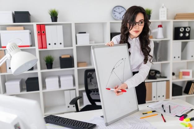 Una bella ragazza si trova vicino a una scrivania e disegna un pennarello magnetico sulla lavagna magnetica.