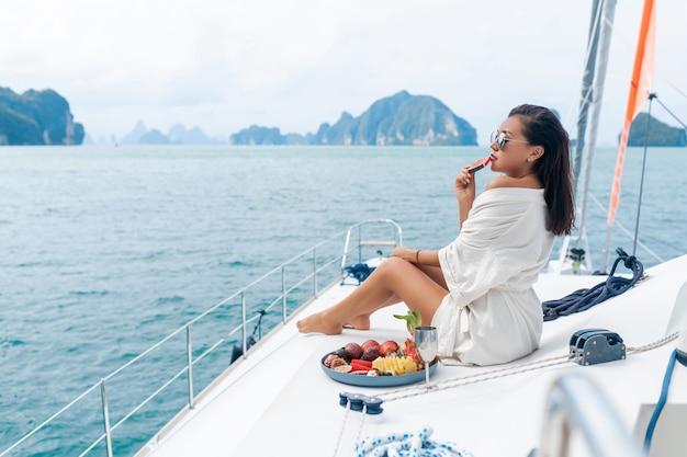 Una bella signora asiatica in un accappatoio bianco su uno yacht beve champagne e mangia frutta, mare