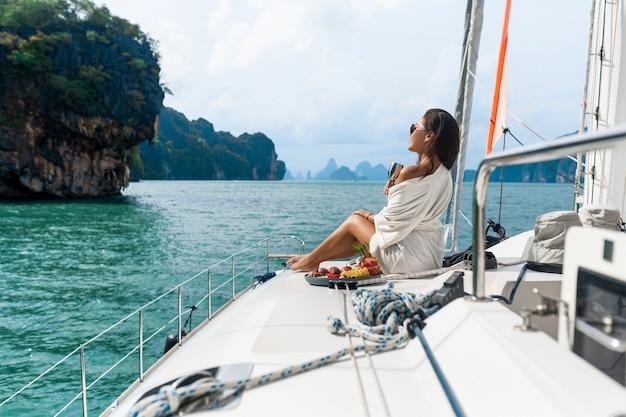 Una bella signora asiatica in una camicia bianca su uno yacht beve champagne e mangia frutta