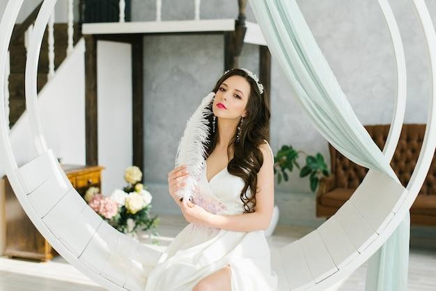 Una bella sposa bruna tiene in mano una penna e si tocca il viso con una penna. la mattina del boudoir della sposa