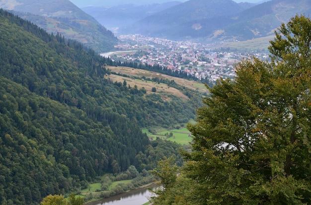 Una bella vista del villaggio di mezhgorye, regione dei carpazi. un sacco di edifici residenziali circondati da alte montagne forestali e lungo fiume
