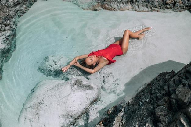 Una bellissima bionda snella in un costume da bagno rosso alla moda si trova nel mare, vicino alle rocce. moda tropicale.