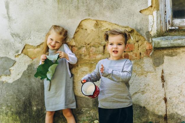 Una bellissima coppia di bambini in abiti grigi sta giocando sullo sfondo del muro