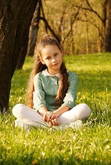 Una bellissima giovane bambina sorridente, seduta nel parco sull'erba