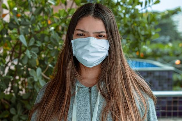 Una bellissima giovane donna con mascherina chirurgica, protetta dalla pandemia a casa sua