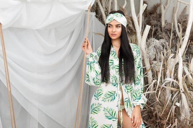 Una bellissima giovane donna in una tunica da spiaggia alla moda