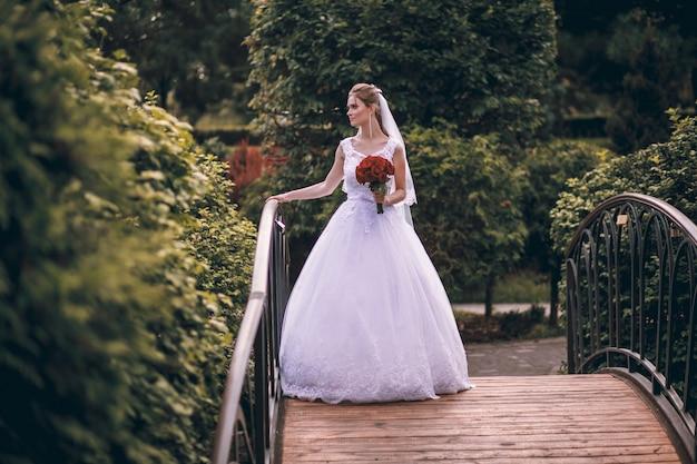 Una bellissima giovane sposa bionda si erge su un ponte in un parco esotico, in un lungo abito bianco con un mazzo di fiori in mano, una passeggiata dopo la cerimonia nuziale.