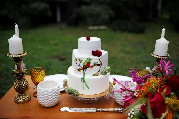 Una bellissima torta nuziale a tre livelli decorata con uccelli, fiori rosa e rami con foglie verdi in stile rustico. dessert festivo concetto di matrimonio.