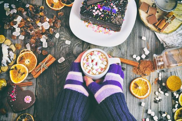 Una bevanda al cacao con fette di marshmallow in mani umane