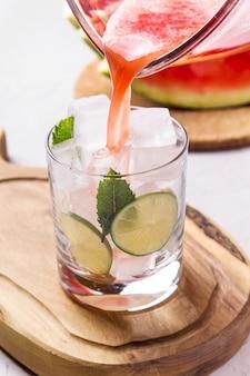 Una bevanda estiva rinfrescante di succo di anguria con lime e ghiaccio
