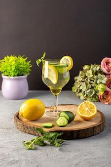 Una bevanda fresca fresca del cocktail del limone di vista frontale dentro la paglia dei limoni affettata vetro sullo scrittorio di legno e la frutta grigia della bevanda del cocktail del fondo