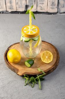 Una bevanda fresca fresca del cocktail del limone di vista frontale dentro la tazza di vetro ha affettato la paglia dei limoni sullo scrittorio di legno e la frutta grigia della bevanda del cocktail del fondo