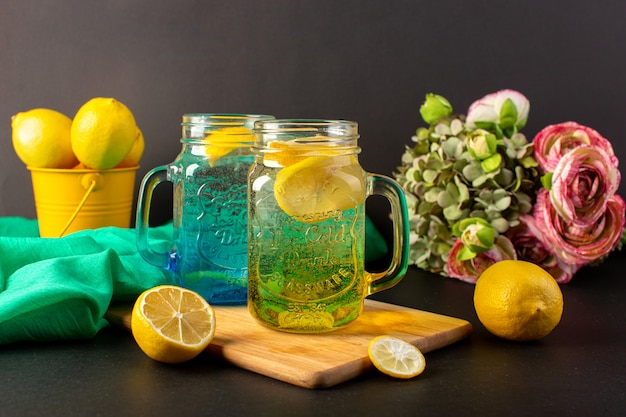 Una bevanda fresca fresca del cocktail del limone di vista frontale dentro le tazze di vetro affettate e limoni interi con i fiori sui precedenti scuri bevono la frutta del cocktail