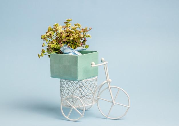 Una bici giocattolo trasporta fiori. l'idea per una cartolina. blu. minimalismo.