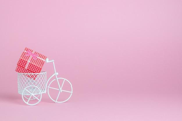 Una bici giocattolo trasporta un regalo. l'idea per una cartolina.