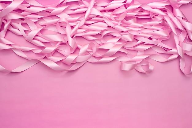 Una bobina di nastri decorativi di raso di colore rosa.