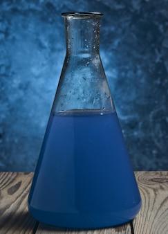 Una boccetta del laboratorio con un liquido blu su una mensola di legno contro un muro di cemento.