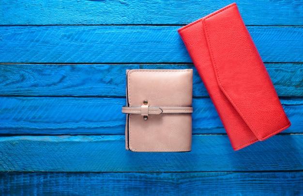 Una borsa delle due donne su un fondo di legno blu. copia spazio. accessori di tendenza. vista dall'alto.