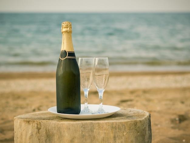 Una bottiglia di bicchieri di champagne freddi e fragole su una spiaggia di sabbia.