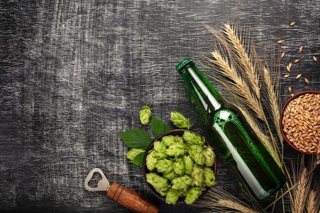 Una bottiglia di birra con luppolo verde, spighette, avena e apribottiglie su una lavagna nera graffiata