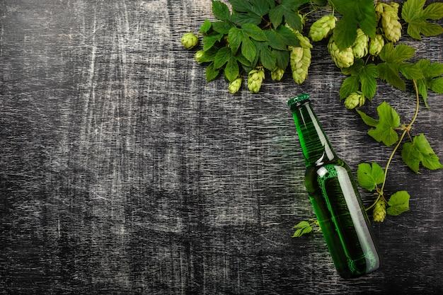 Una bottiglia di birra con un mazzo di luppolo fresco verde su un bordo di gesso graffiato nero
