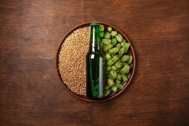 Una bottiglia di birra su un grano verde fresco del grano e del luppolo in un piatto contro il bordo marrone di legno